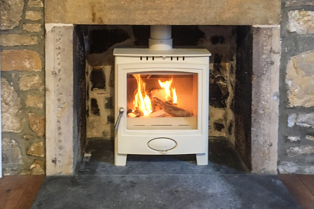 Cream multifuel stove fitted in fisherman's cottage in Findhorn