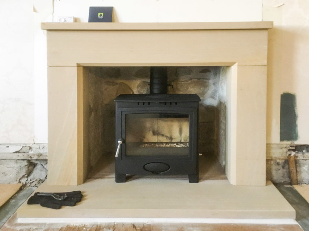 Local sandstone fireplace with a multifuel stove in Lossiemouth